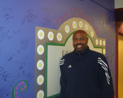 Mike Powell poses near the artist wall