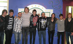 Both bands pose together in front of the Artist Wall