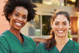 two health care workers smiling