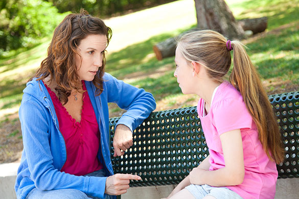 Mother-Listening-to-Daughter-in-Park
