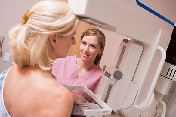 technician assisting patient with mammogram