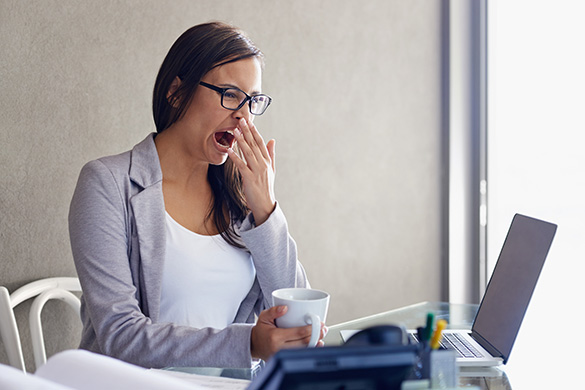 young woman sitting at her desk yawning