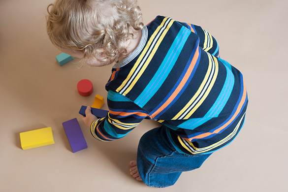 toddler picking up blocks