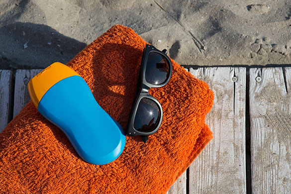 Sunscreen and Glasses sitting on a towel on the beach