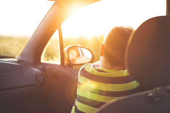 Child sitting in a car with the sun shining in the window