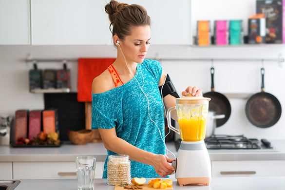 woman making smoothie after exercise