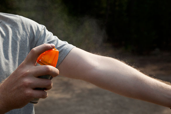 Man spraying insect repellent on his arm