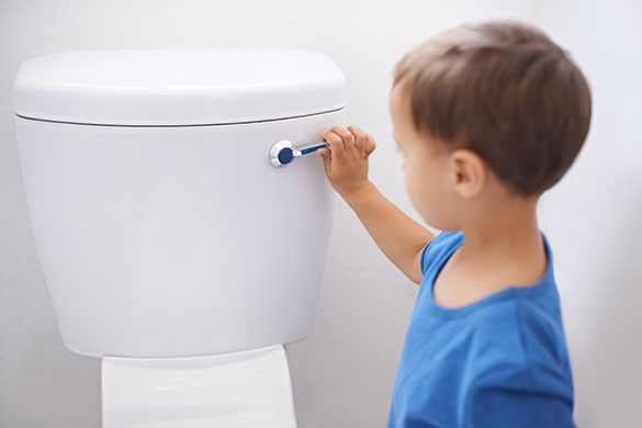 Young boy flushing a toilet