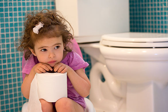 Little girl sitting on potty chair with toilet paper in her hands