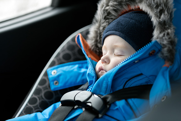infant bundled up in a car seat