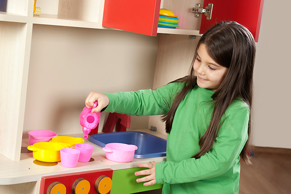 preschooler playing in toy kitchen