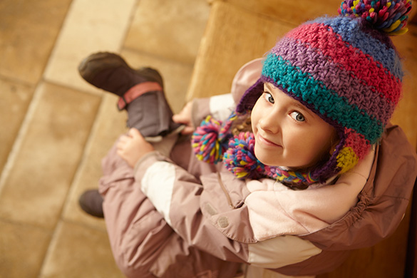 child dressing herself in winter clothes