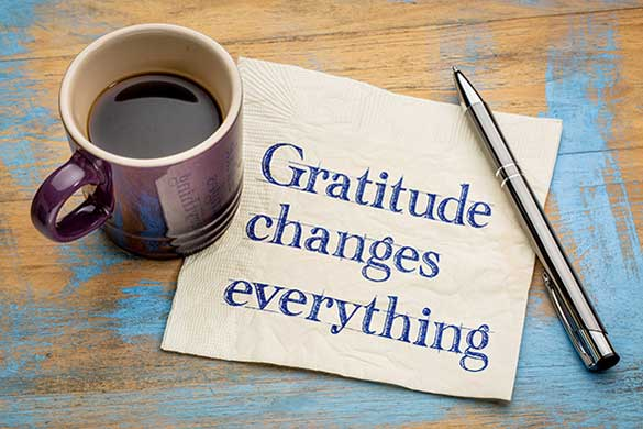 Gratitude changes everything on napkin, with coffee cup and pen
