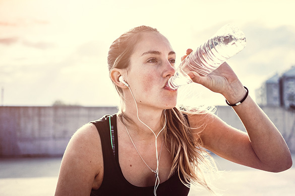 young woman drinking water during exercise