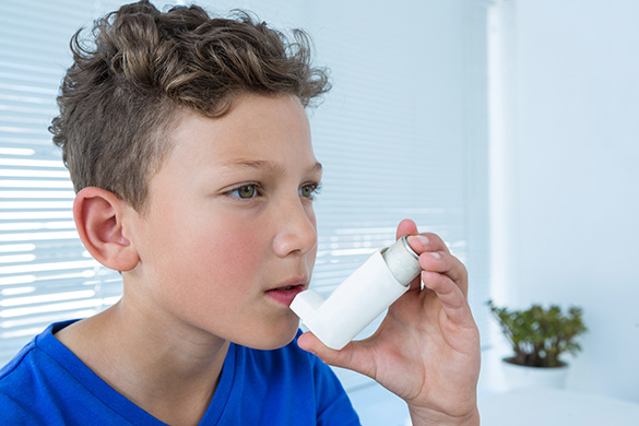 boy using an inhaler for asthma