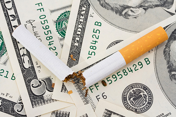 broken cigarette laying on top of money