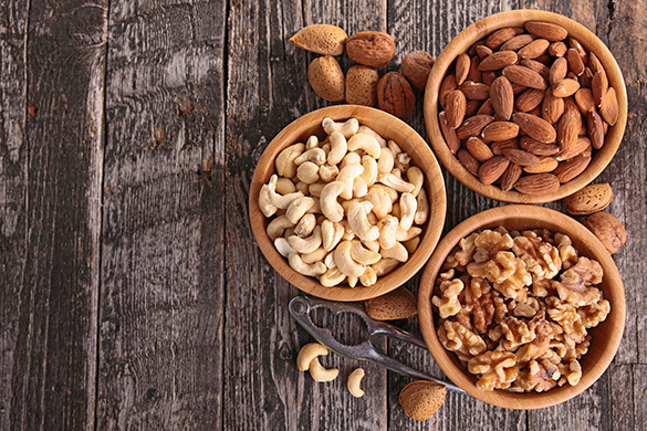 bowls of almonds, cashews and walnuts