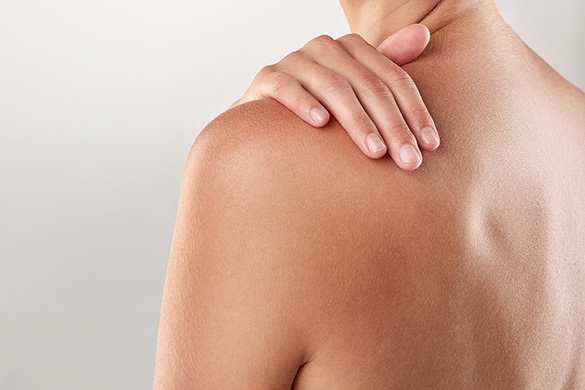 woman's bare back with her hand on shoulder