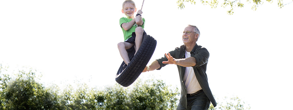 Grandpa push child on tire swing