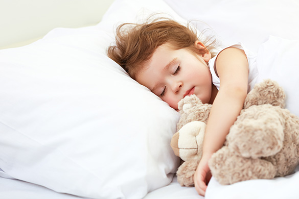 child sleeping with her teddy bear