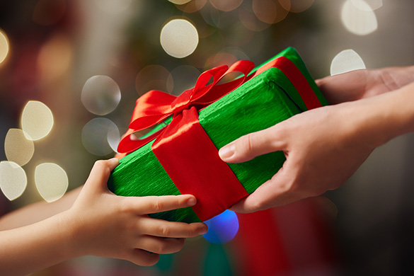 parent giving christmas gift to a child