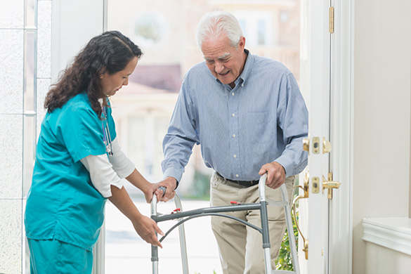 healthcare worker helping man with walker