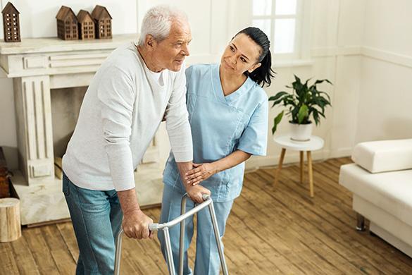 caregiver helping man use a walker