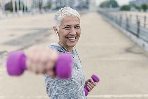 woman exercising with pink dumbbells