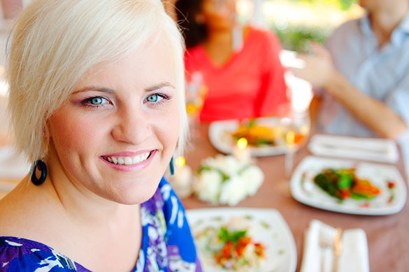 woman smiling at camera dining with friends