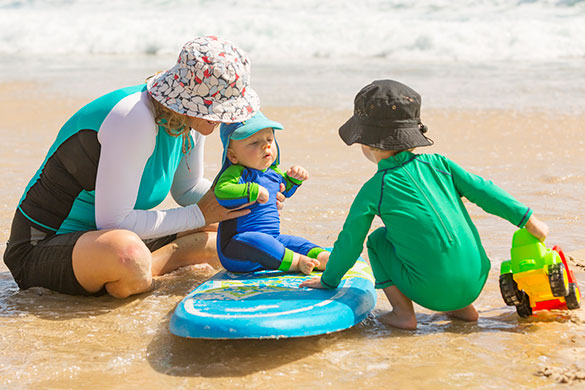 woman with kids on beach wearing protective clothing and hats