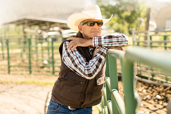 rancher wearing cowboy hat leaning on fence