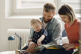 mother, father and young child reading