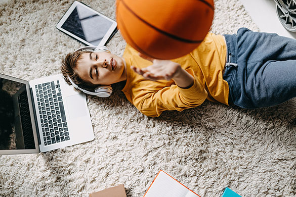 boy laying on floor wearing headphones throwing basketball