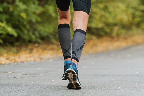 back view of runners lower legs wearing compression calf sleeves
