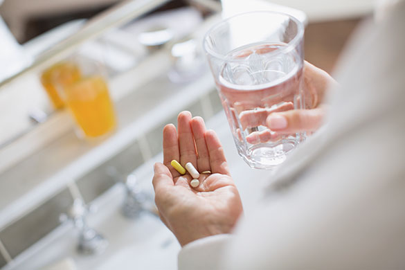 closeup of womans hands holding vitamins and glass of water