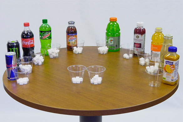 bottles of drinks on table with sugar content comparison