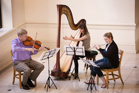three musicians playing a harp, violin and flute