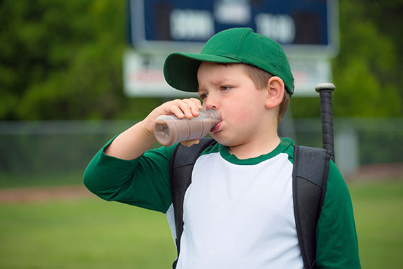 boy drinking chocolate milk after playing baseball
