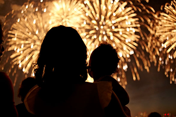 silhouette of mother and daughter watching fireworks