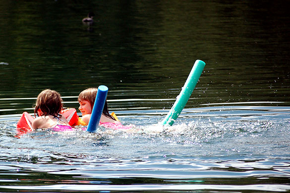 two girls using floaties as they swim on a lake