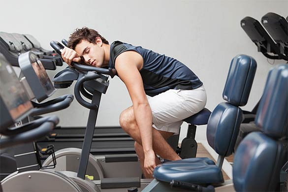 Male athlete sleeping on stationary bicycle
