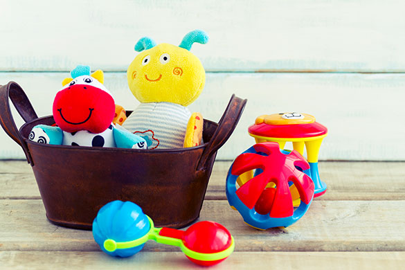 baby toys in a basket and on wood floor