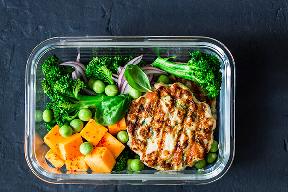 stuffed chicken burger and veggies in glass container