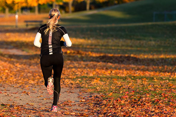 rear view of woman running outdoors during fall