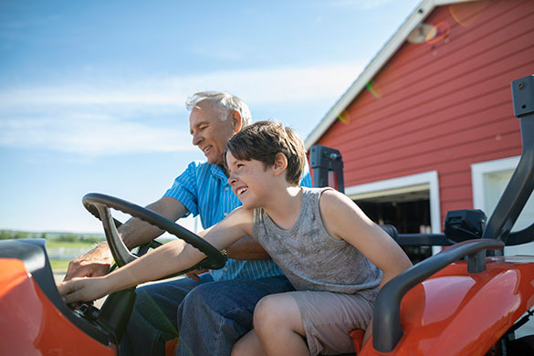 grandfather and grandson sitting on tractor at farm