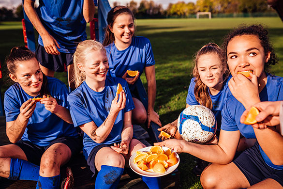 teen girls eating oranges after soccer practice