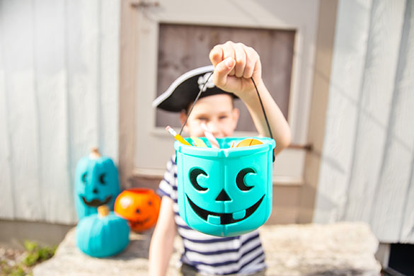 boy in pirate costume holding teal colored halloween bucket