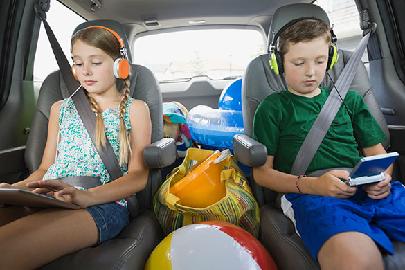siblings in car wearing headphones using digital devices