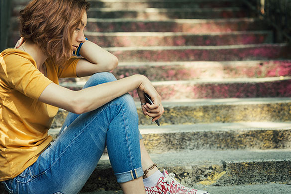 teen girl sitting on stairs arms on knees