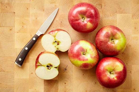 apples on a cutting board with knife